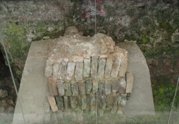 piece of excavated wall within the white brick wall